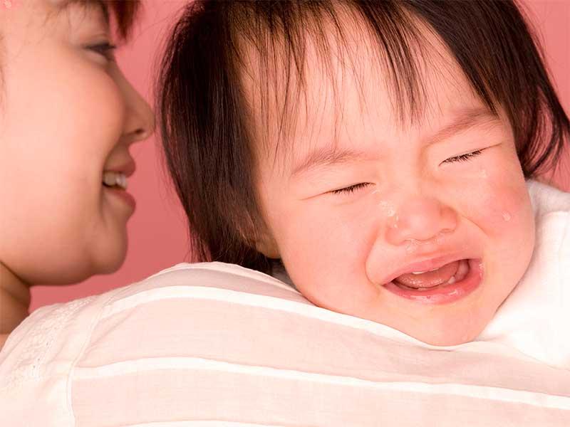 ゲップをするためにママに抱っこされてるけど泣いてる赤ちゃん