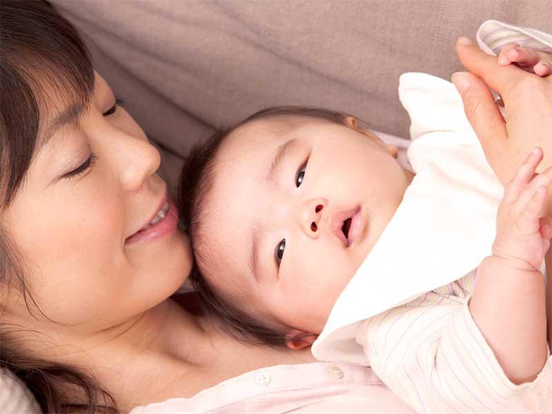 新生児を抱っこしているママ