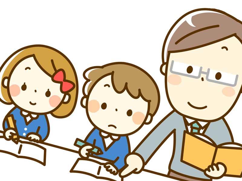 小学校で先生から授業を受けている1年生