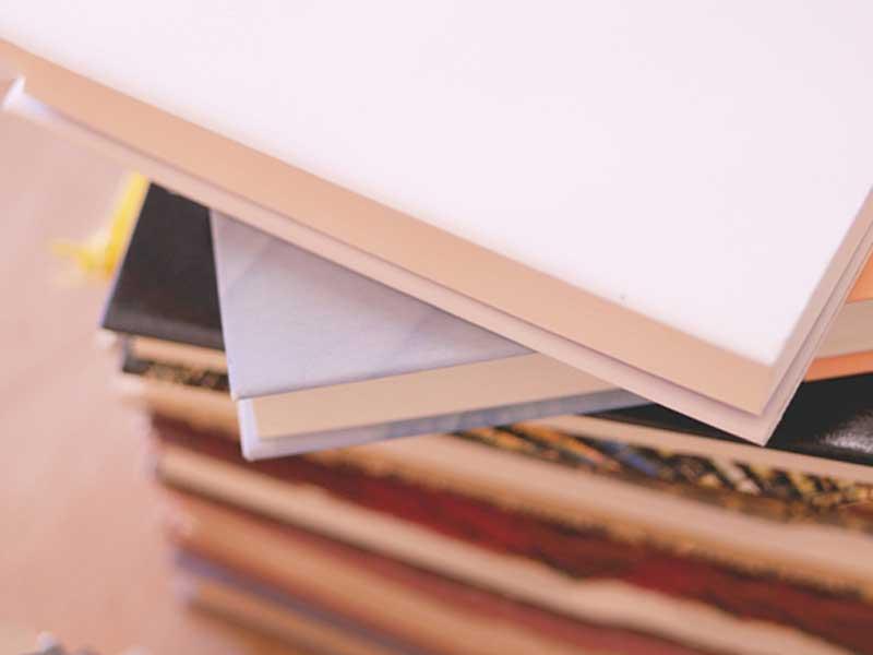 机の上に重なっている多数の教科書