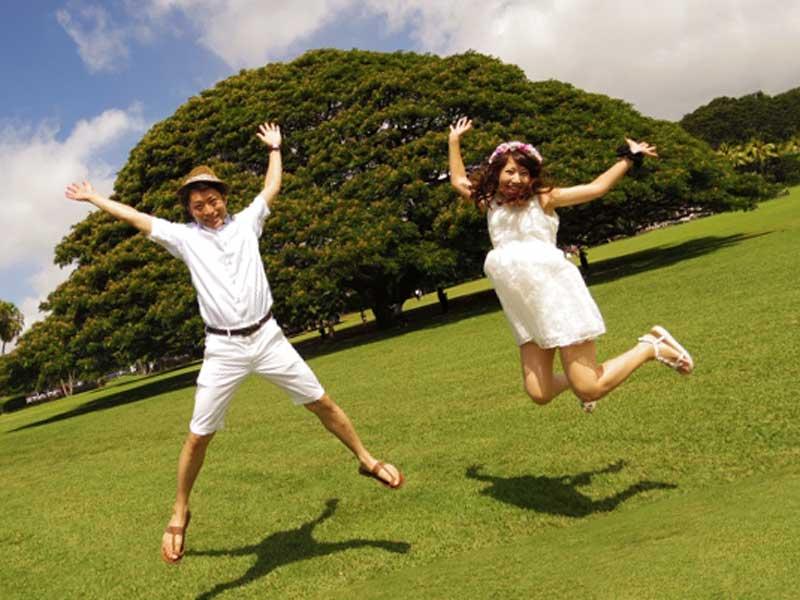草原でジャンプして記念撮影している仲がいい夫婦