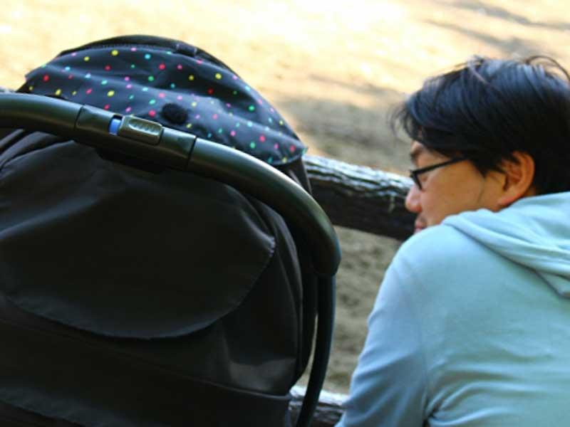 ベビーカーの中にいる赤ちゃんを連れて散歩するお父さん