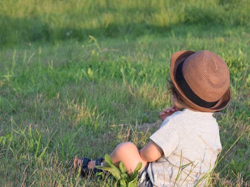 芝の上に座って遠くを見つめる子供