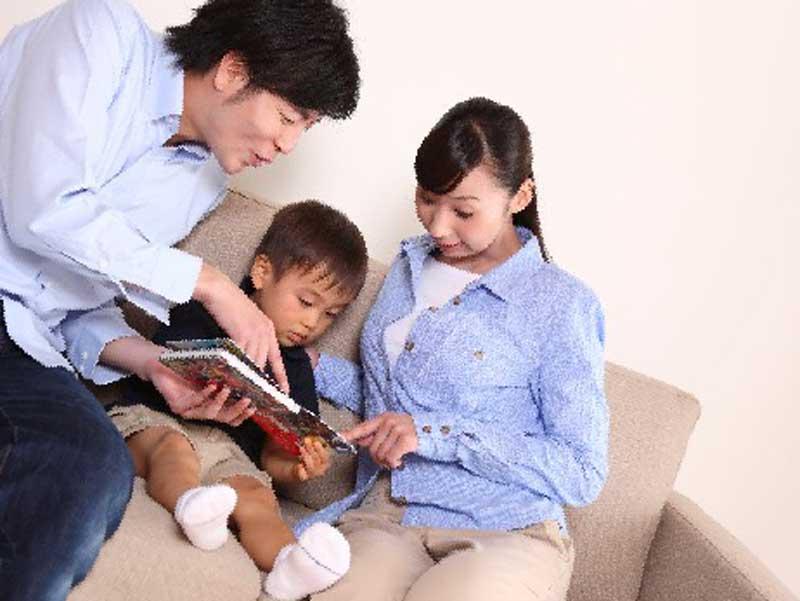仲良く子供に絵本を読む夫婦