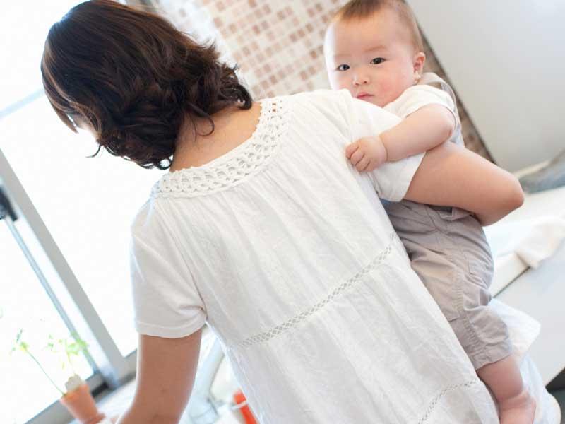 赤ちゃんを抱っこしてキッチンに立っている赤ちゃん