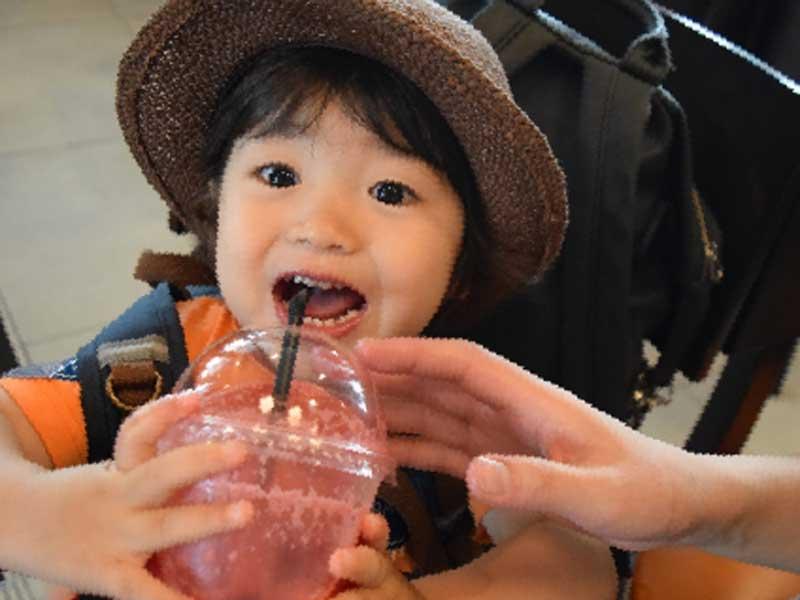 旅行先でストローでジュースを飲んでいる子供