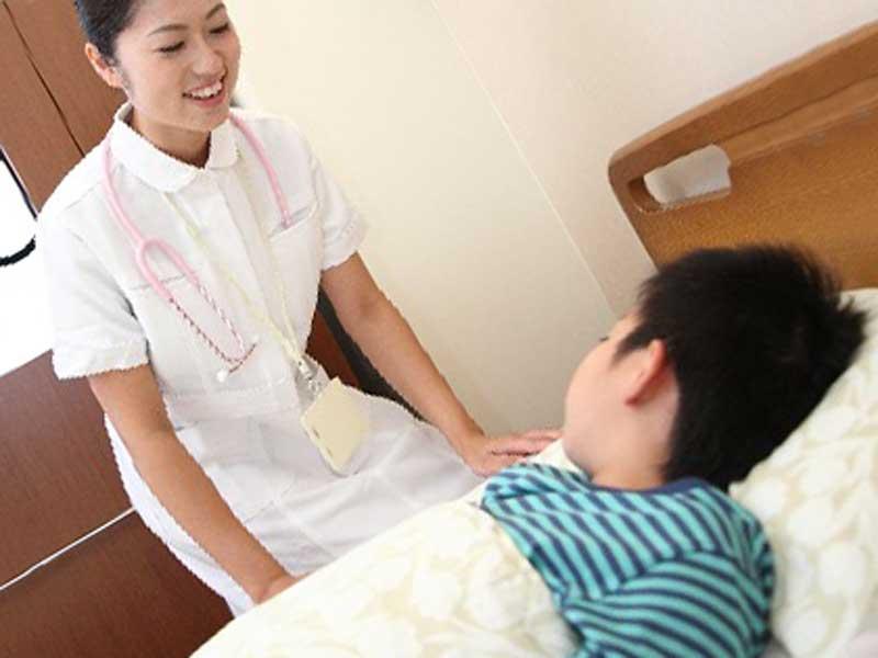 入院している男の子と看護師
