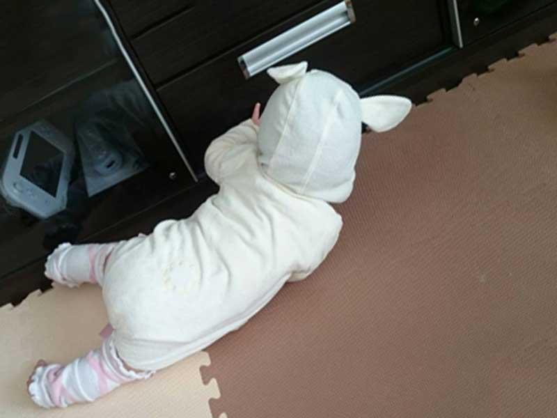 家具をつかんで起きろとする赤ちゃん
