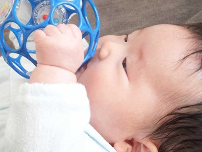 おもちゃを掴んで遊んでいる赤ちゃん