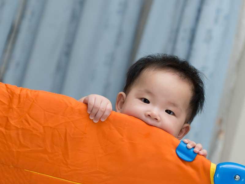 ベビーサークルの中で遊ぶ赤ちゃん