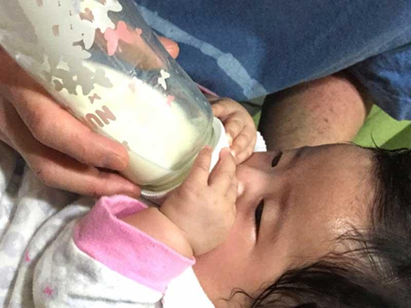 赤ちゃんに授乳をしているお父さん