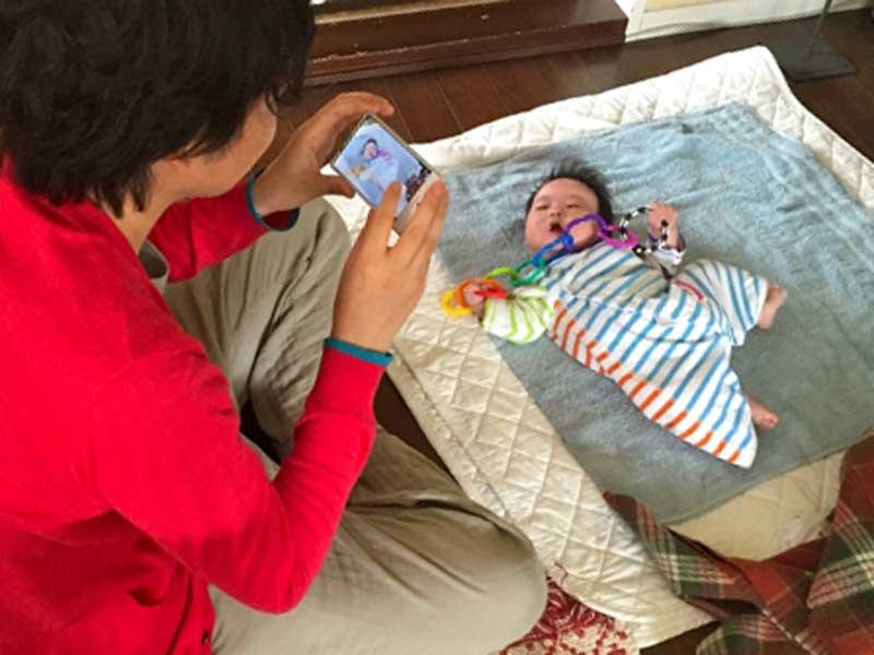 新生児の赤ちゃんの写真を撮っているお父さん