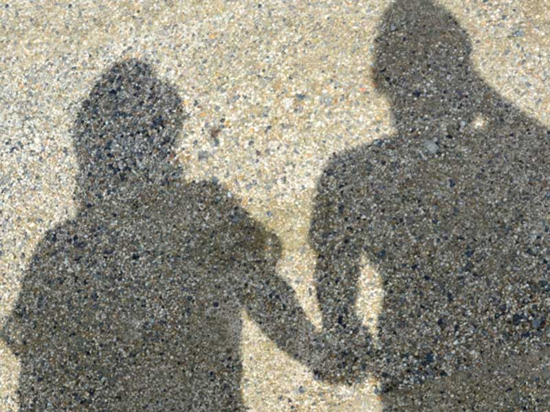 砂浜で手を繋いでいる夫婦