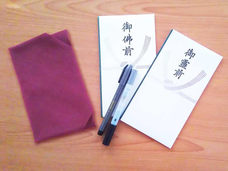 不祝儀袋、薄墨の筆ペンと香典を包む袱紗