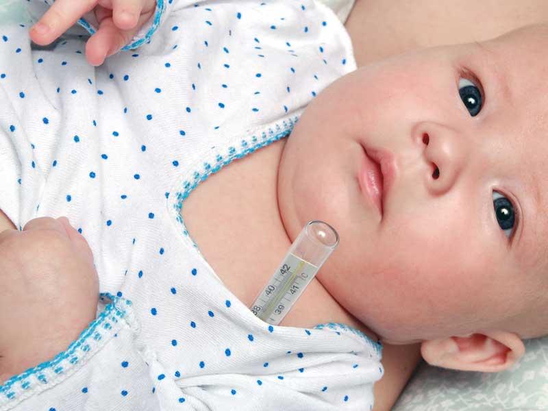体温計を脇に挟んでいる赤ちゃん