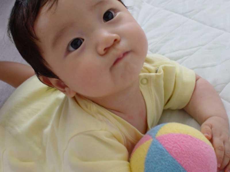 色付きのおもちゃを遊んでいる赤ちゃん