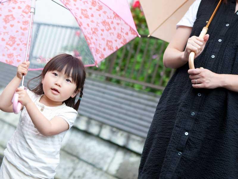 傘を持って走る子供を追いかける妊婦さん