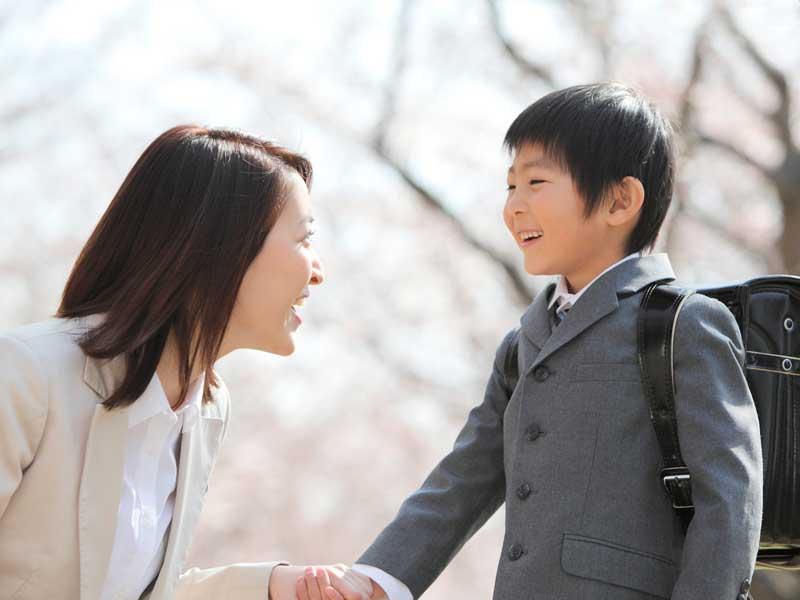 小学校に入学する子供の手を繋ぐお母さん