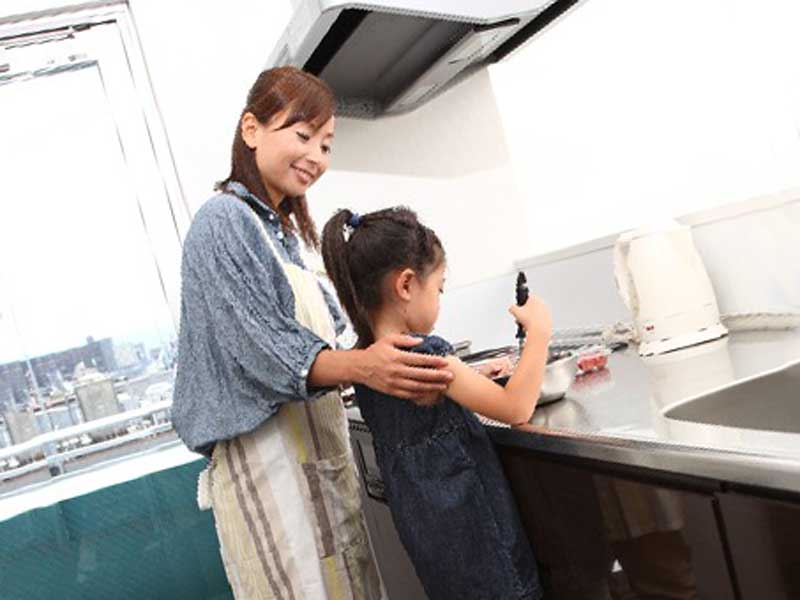 料理をしている子供とお母さん