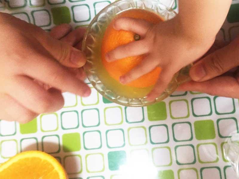 オレンジ搾りを手伝う子供