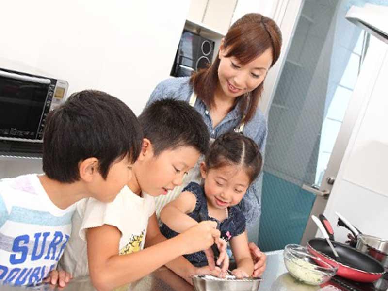 料理をしている三人の子どもとお母さん