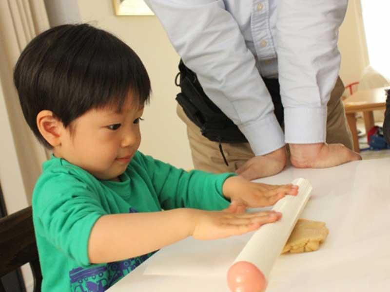 クッキーの生地を伸ばしている子供