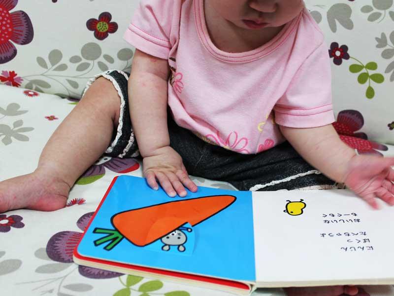 自分で絵本をめくりながら見ている赤ちゃん