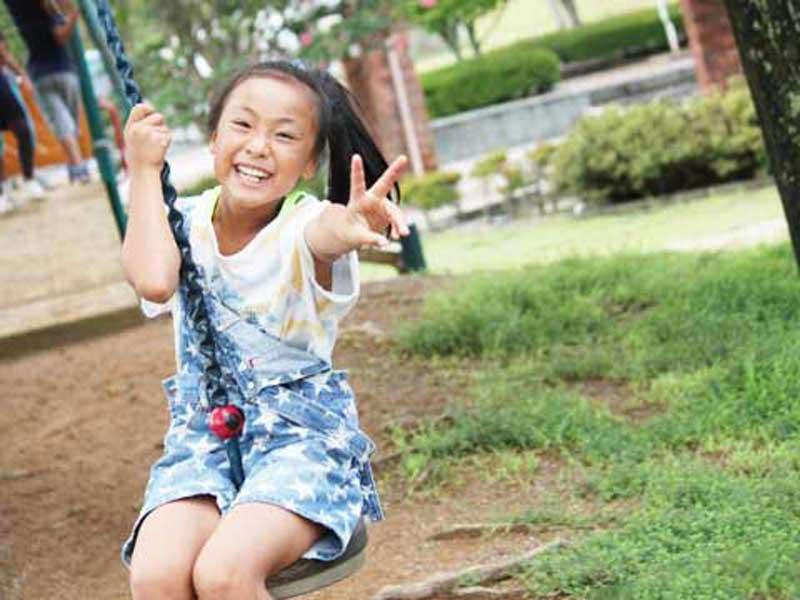 ブランコで楽しく遊んでいる女の子
