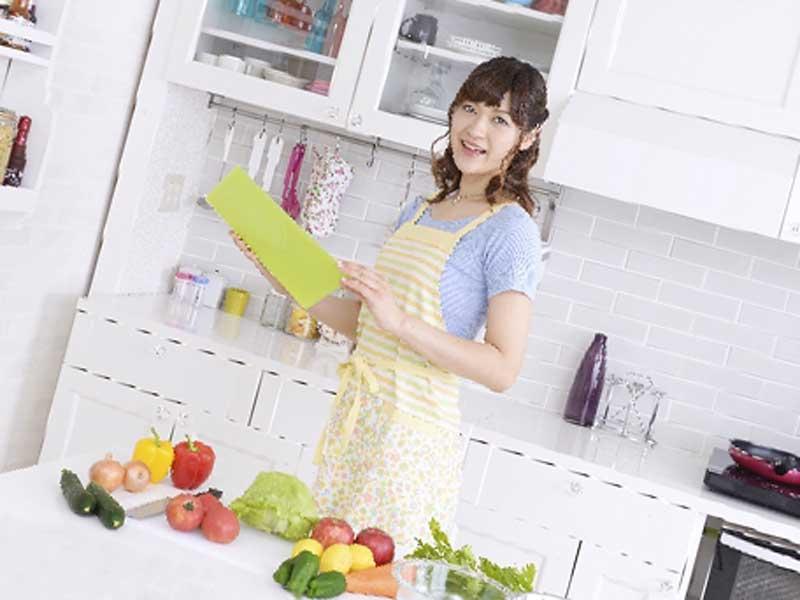 レシピを見ながら料理を作る女性