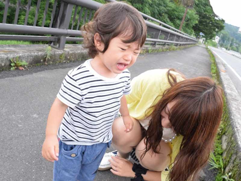 保育園に行く途中で泣いている子供とお母さん