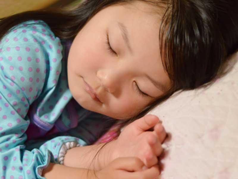 枕で寝ている子供