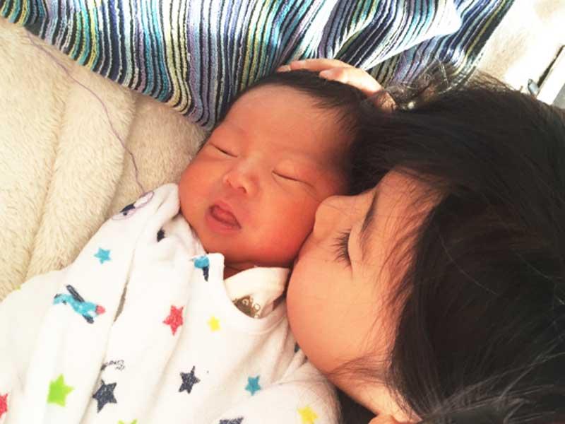 寝ている赤ちゃんをチューするお姉さん