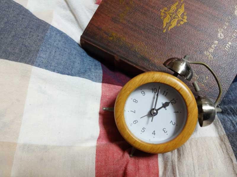ベッドの上に置いてある目覚まし時計