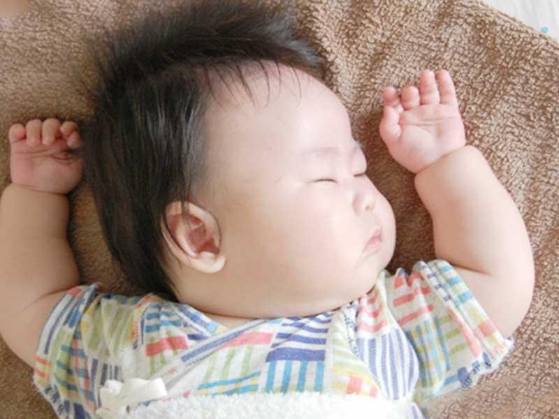 片方のほっぺをつけて寝ている赤ちゃん