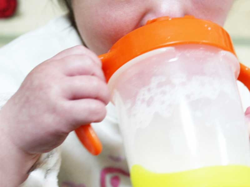 マグでミルクを飲んでいる赤ちゃん