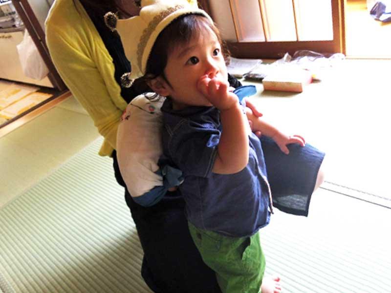 一升餅を背負って歩いている赤ちゃん