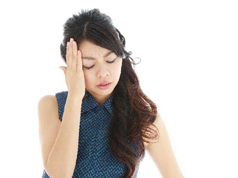 偏頭痛で頭に手をあてている妊婦さん