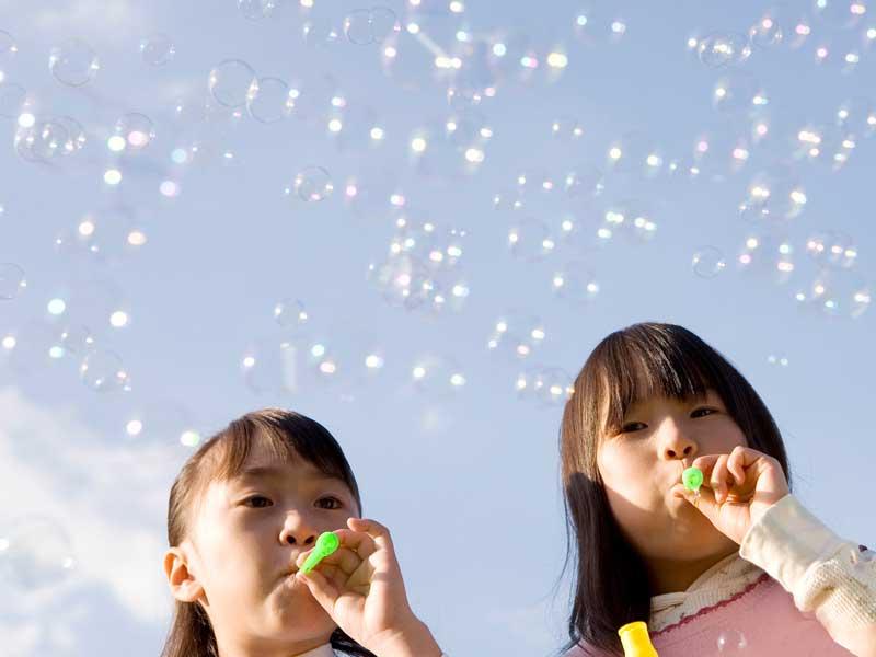 シャボン玉で遊んでいる小学生達
