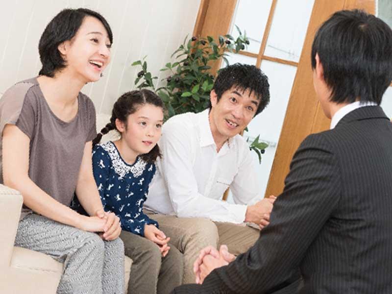 家庭訪問する先生と小学生の両親