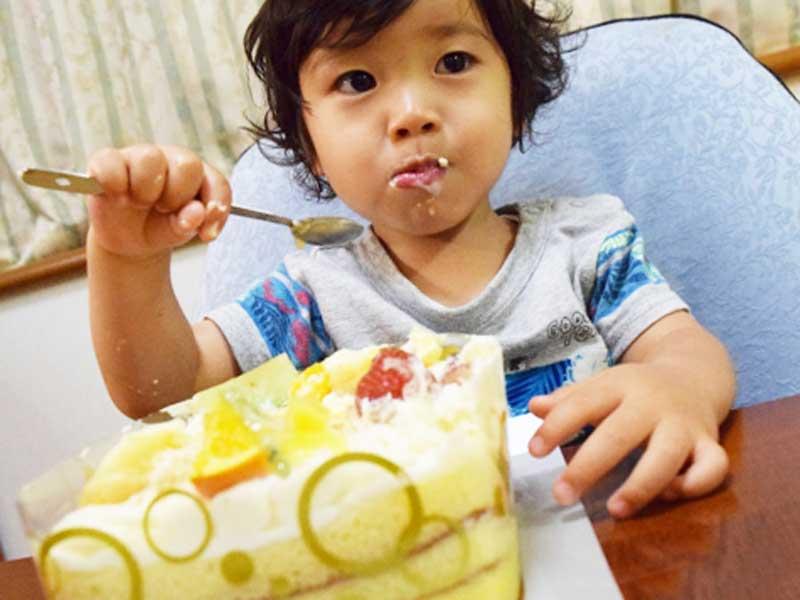 誕生日ケーキを食べる子供