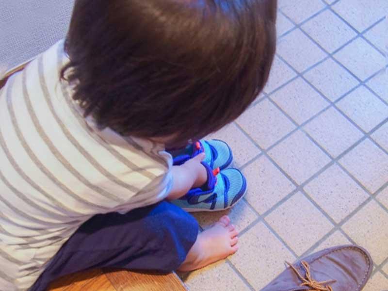 自分で靴を履いている子供