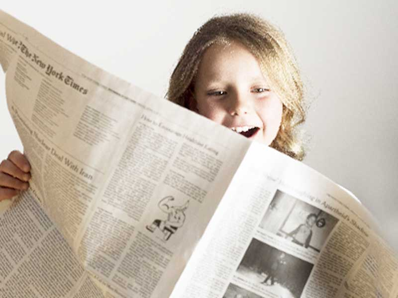 子供用の新聞を読んでいる女の子
