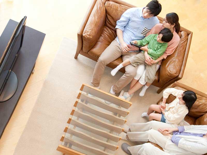 テレビでニュースを見ている家族