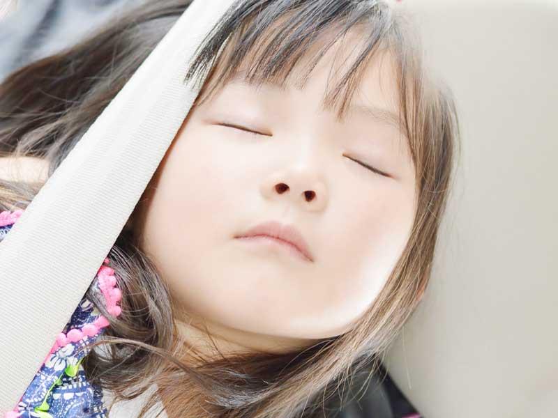 車の中で寝ている子供