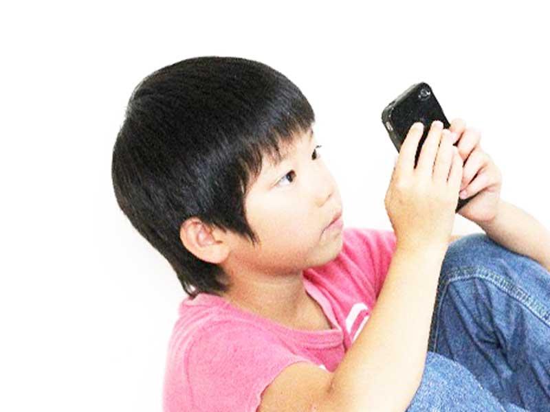 スマホでゲームをしている子供