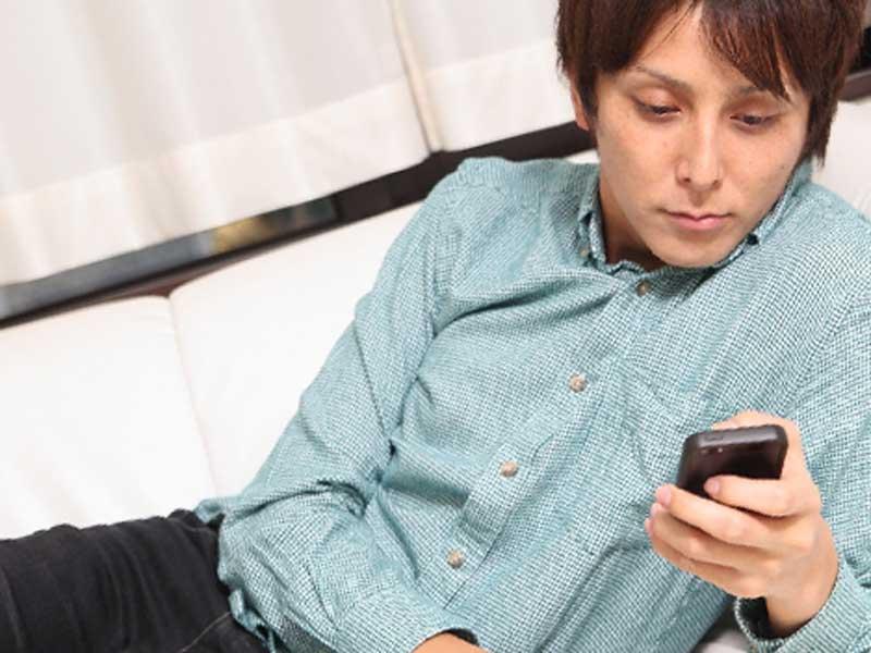 携帯電話でゲームを遊んでいるパパ
