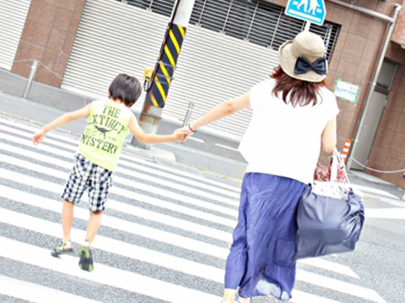 子供を連れて横断歩道を渡るお母さん