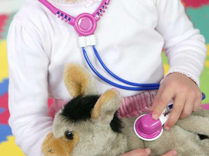 ヌイグルミを使ってお医者さんごっこで遊んでいる女の子
