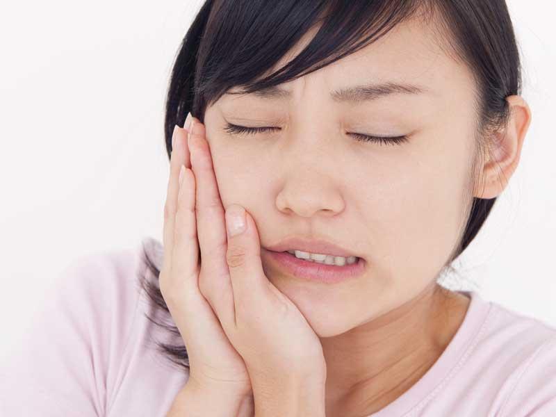 歯を痛がっているお母さん