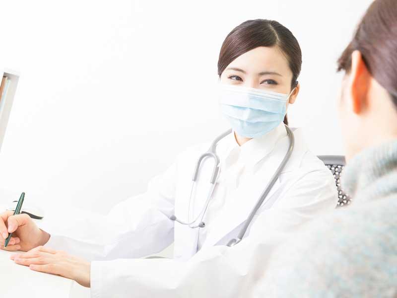 病院のかかりつけ医と相談するお母さん